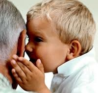 Child whispering into Grandpa's ear