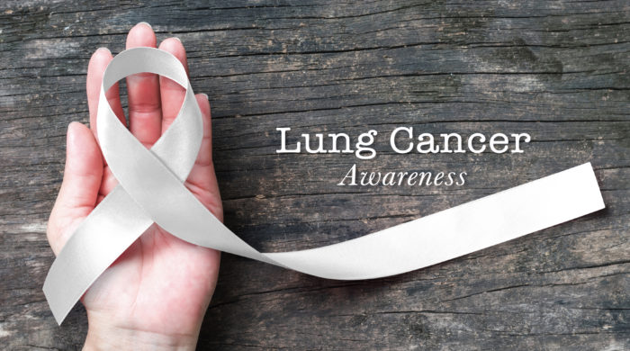 Lung cancer awareness month with white/ light pearl color ribbon on woman's hand support on aged wood